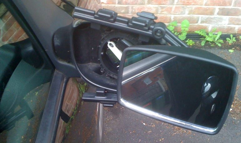 A broken wing mirror with caravan extender attached